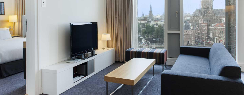 Deze suite met aparte slaapkamer en zitruimte, uitgerust met televisie en sofa, kijkt uit op het bruisende centrum van Amsterdam