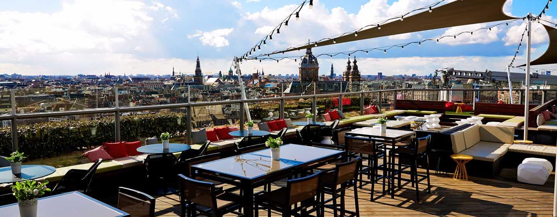Op het dakterras van de Sky Lounge kijkt u als een adelaar uit over alle daken en grachten van de stad Amsterdam
