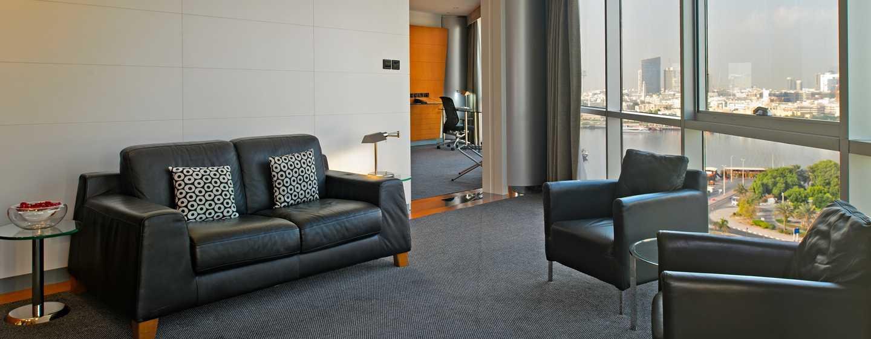 Hilton Dubai Creek Hotel, VAE– Wohnbereich der Deluxe Suite mit King-Size-Bett