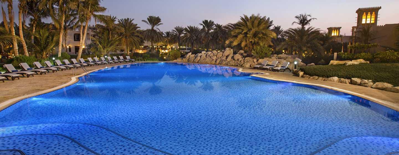 Hilton Al Hamra Beach & Golf Resort -hotelli, Ras Al Khaimah, Yhdistyneet arabiemiirikunnat – uima-allas auringon laskiessa