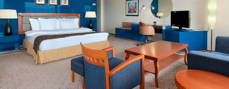 Das großzügige Zimmer verfügt über bequeme Sessel und einen Couchtisch