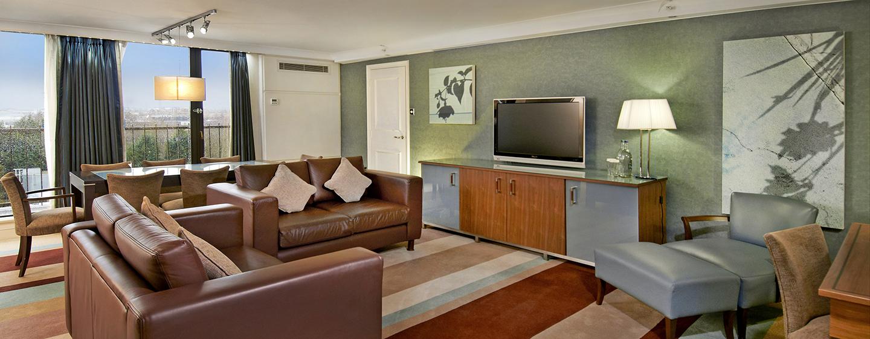 In der Suite steht Ihnen ein separates Wohnzimmer mit einem großen Esstisch zur Verfügung