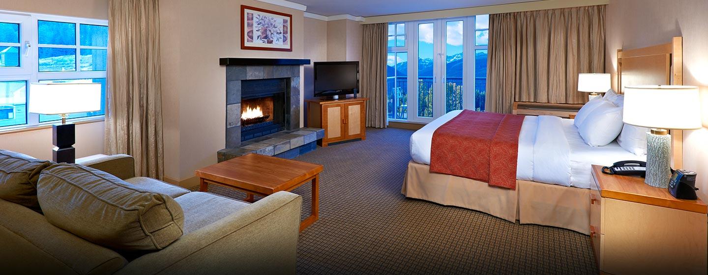 Hôtel Hilton Whistler Resort & Spa, CB - Chambre avec un très grand lit et une cheminée